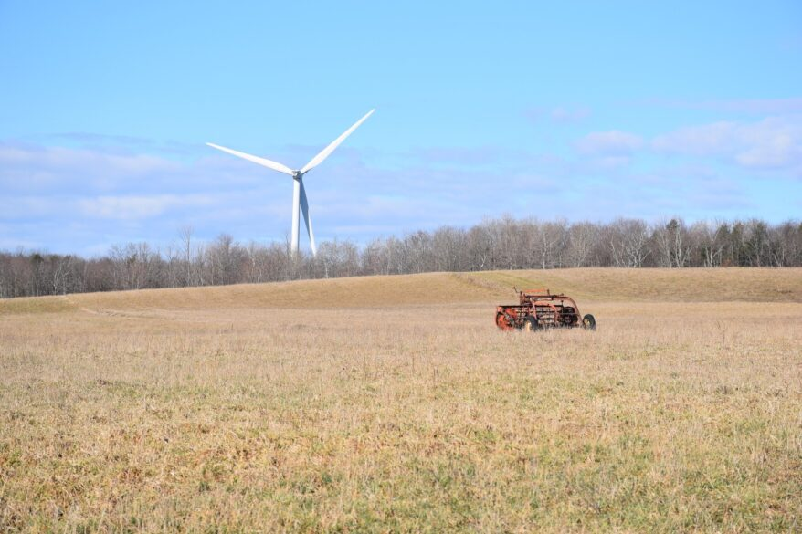 A wind turbine spins behind a field along Turnpike Rd - FLT M11