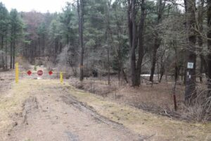 Barrier and parking area at trailhead on Bear Creek Rd, trail heading west