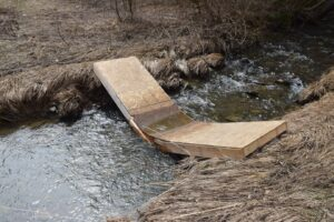 Broken foot bridge over Bear Creek at trailhead, trail heading west